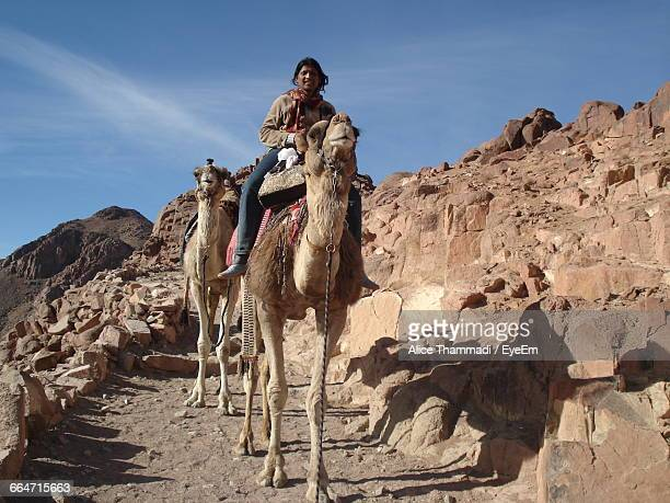 Portrait Of Young Woman Riding Camel On Rock Formation