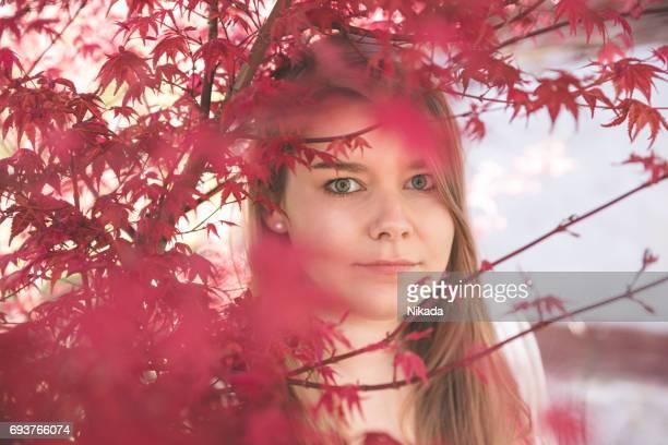 Porträt der jungen Frau, die durch rote Baum gesehen