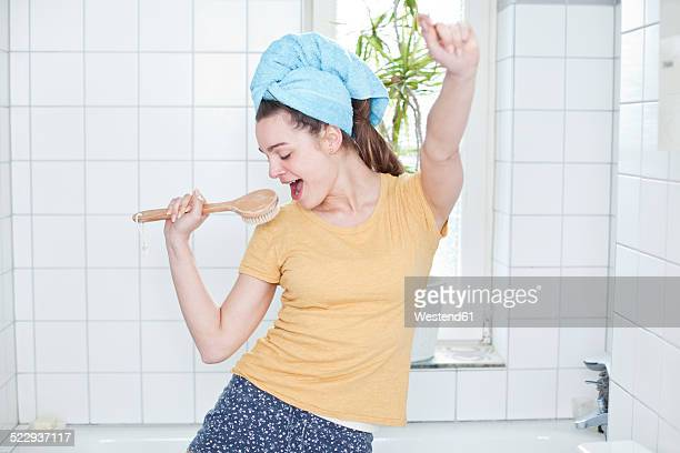 Portrait of young woman singing in the bathroom using massage brush as microphone