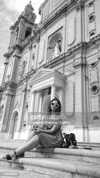 Portrait Of Young Woman Sitting Against St Joseph Church At Msida