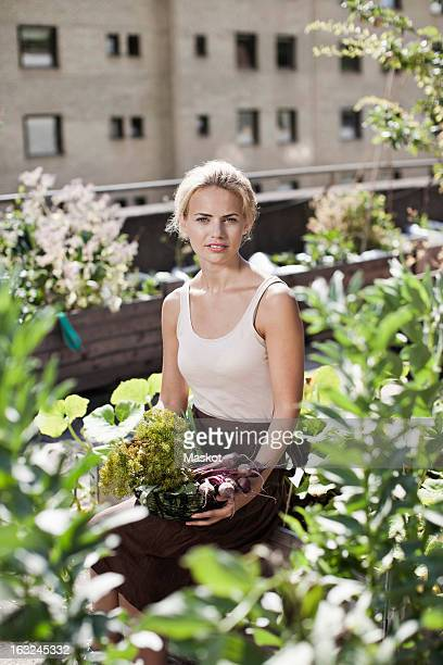 Portrait of young woman sitting at urban garden