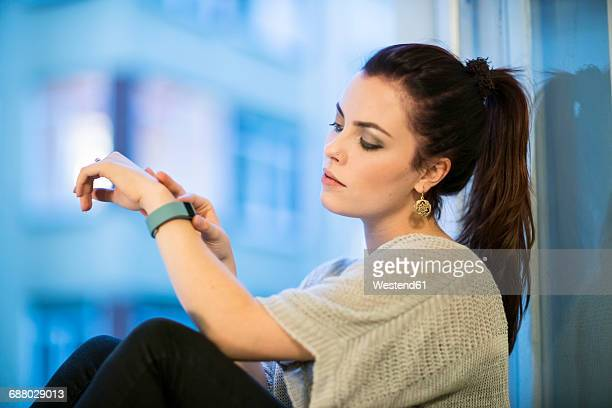 Portrait of young woman sitting beside window looking at smartwatch