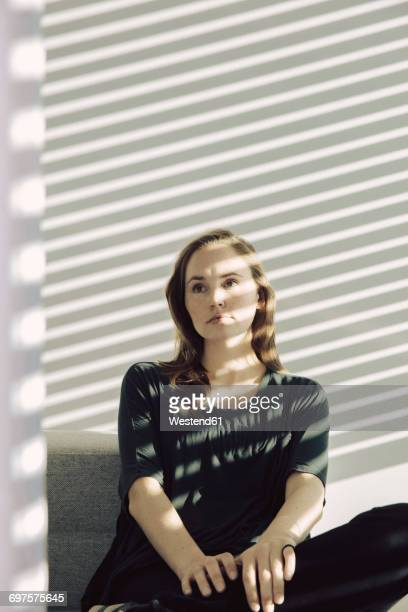 Portrait of young woman sitting in a shadowed room