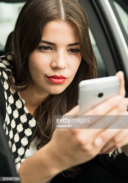 Portrait of young woman sitting in car taking a selfie with her smartphone