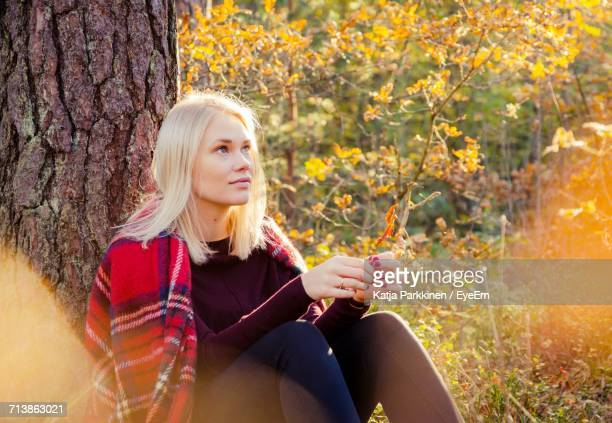 Portrait Of Young Woman Sitting In Forest During Autumn