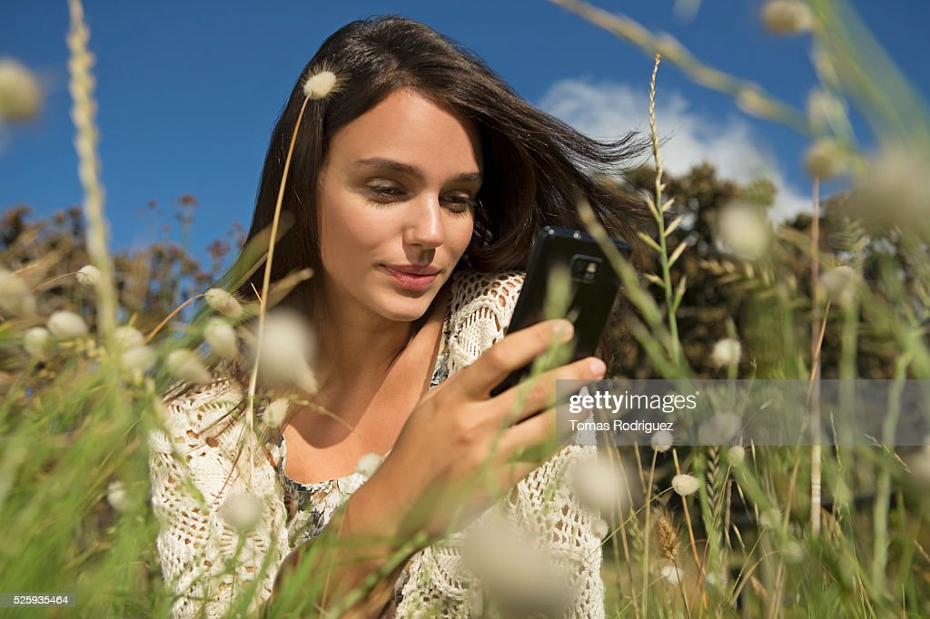Portrait of young woman sitting in grass and using cell phone : ストックフォト