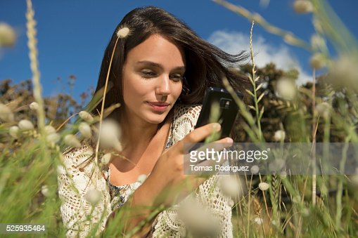 Portrait of young woman sitting in grass and using cell phone : Stock Photo