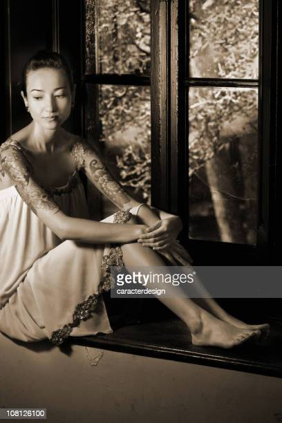 Portrait of Young Woman Sitting in Windowsill, Sepia Toned