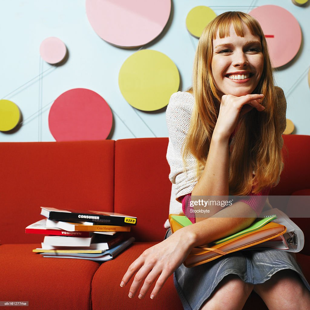 portrait of young woman sitting on a couch with books in her lap : Stock Photo