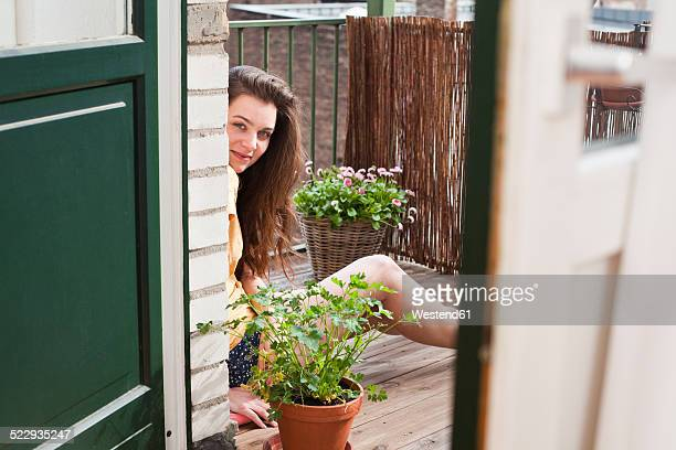 Portrait of young woman sitting on her balcony
