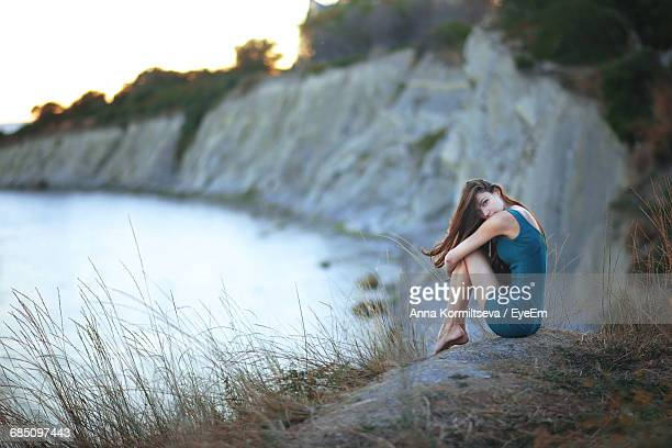 Portrait Of Young Woman Sitting On Hill By Lake