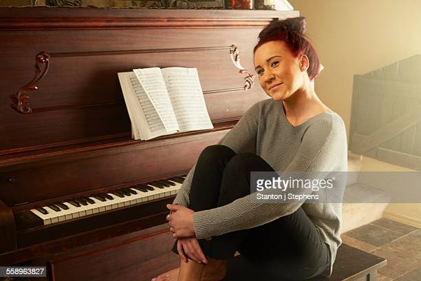 Portrait of young woman sitting on piano stool hugging knees