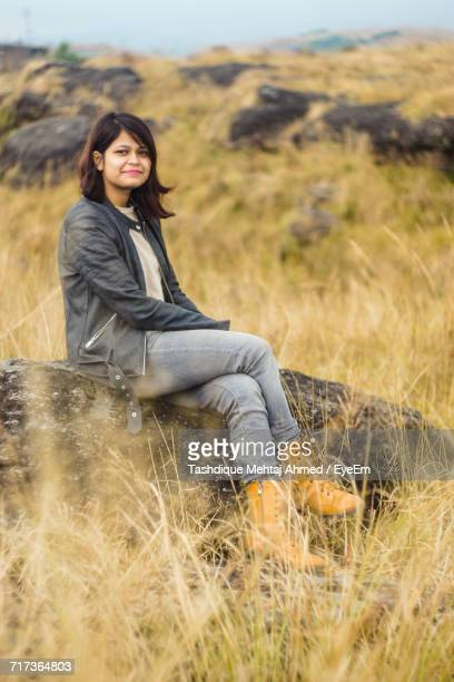 Portrait Of Young Woman Sitting On Rock At Grassy Field