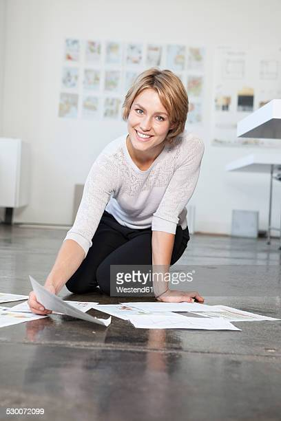 Portrait of young woman sitting on the floor of an office with her concepts