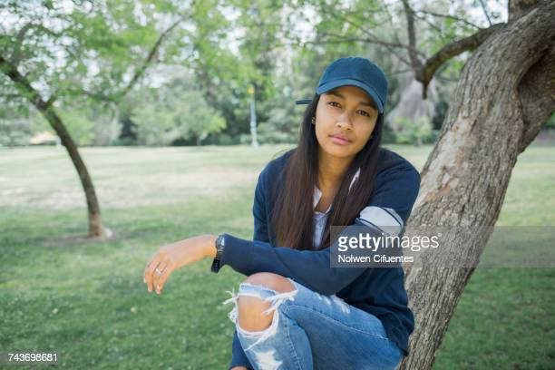 Portrait of young woman sitting on tree trunk at park