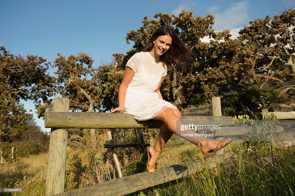 Portrait of young woman sitting on wooden fence : Stock-Foto