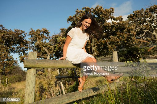 Portrait of young woman sitting on wooden fence : Foto de stock