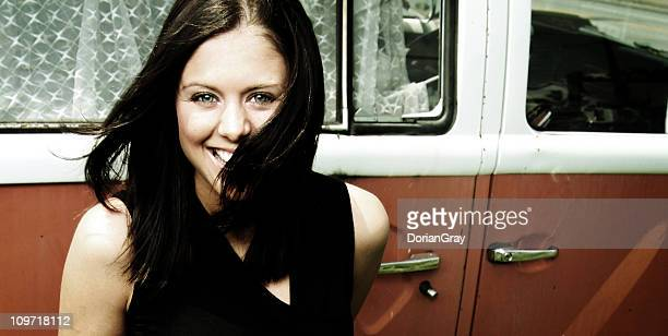 Portrait of Young Woman Smiling Against Old Bus