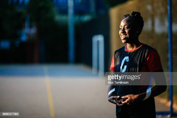 portrait of young woman smiling and wearing netball bib in outdoor, urban sports court