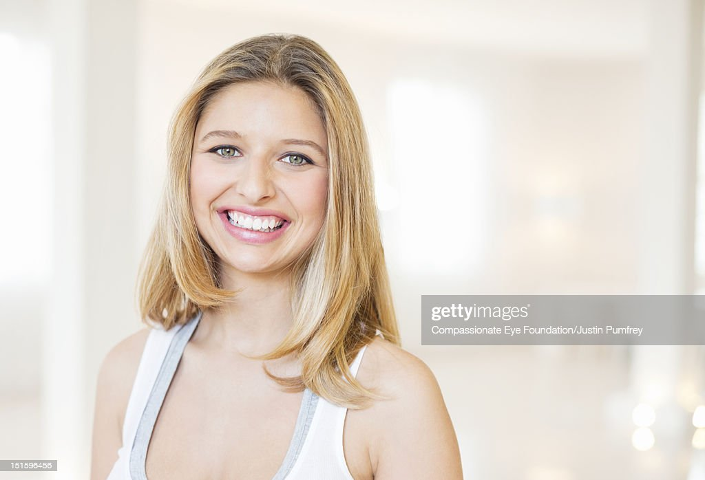 Portrait of young woman smiling, close up : Stock Photo