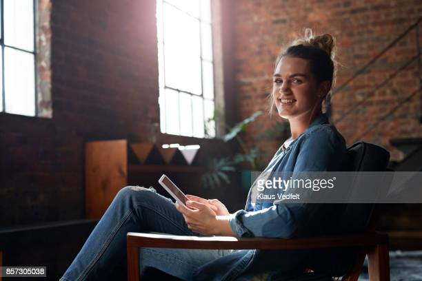 Portrait of young woman smiling to camera, holding tablet