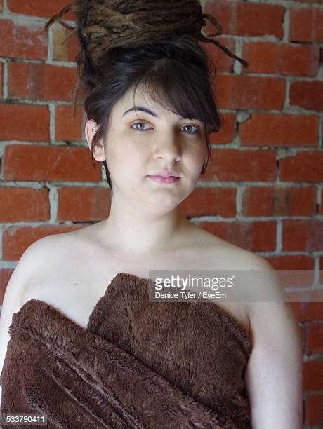 Portrait Of Young Woman Standing Against Brick Wall At Home