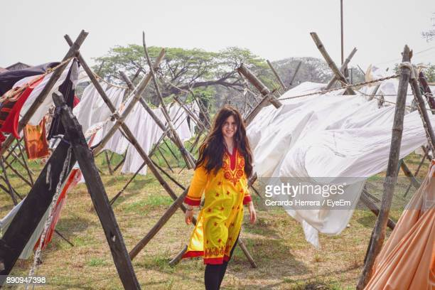 Portrait Of Young Woman Standing Amidst Clothes Drying Outdoors