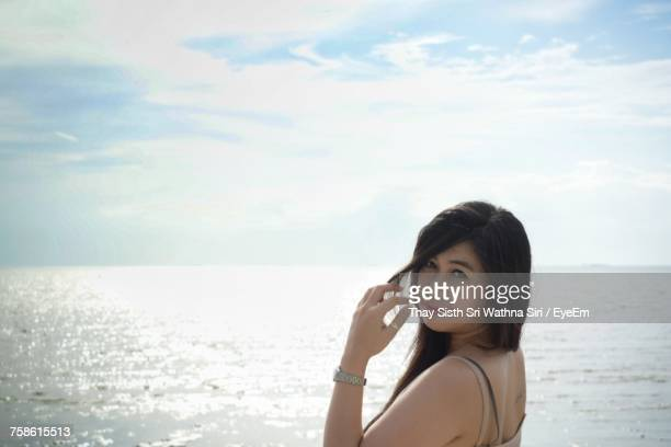 Portrait Of Young Woman Standing At Beach Against Cloudy Sky During Sunny Day