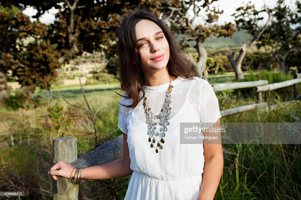 Portrait of young woman standing by fence : Stockfoto