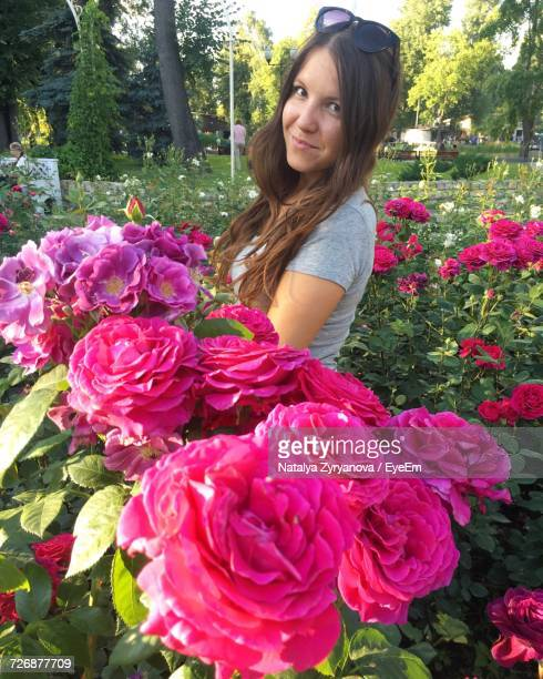 Portrait Of Young Woman Standing By Pink Roses Blooming At Park
