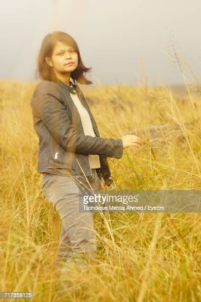 Portrait Of Young Woman Standing On Grassy Field Against Sky