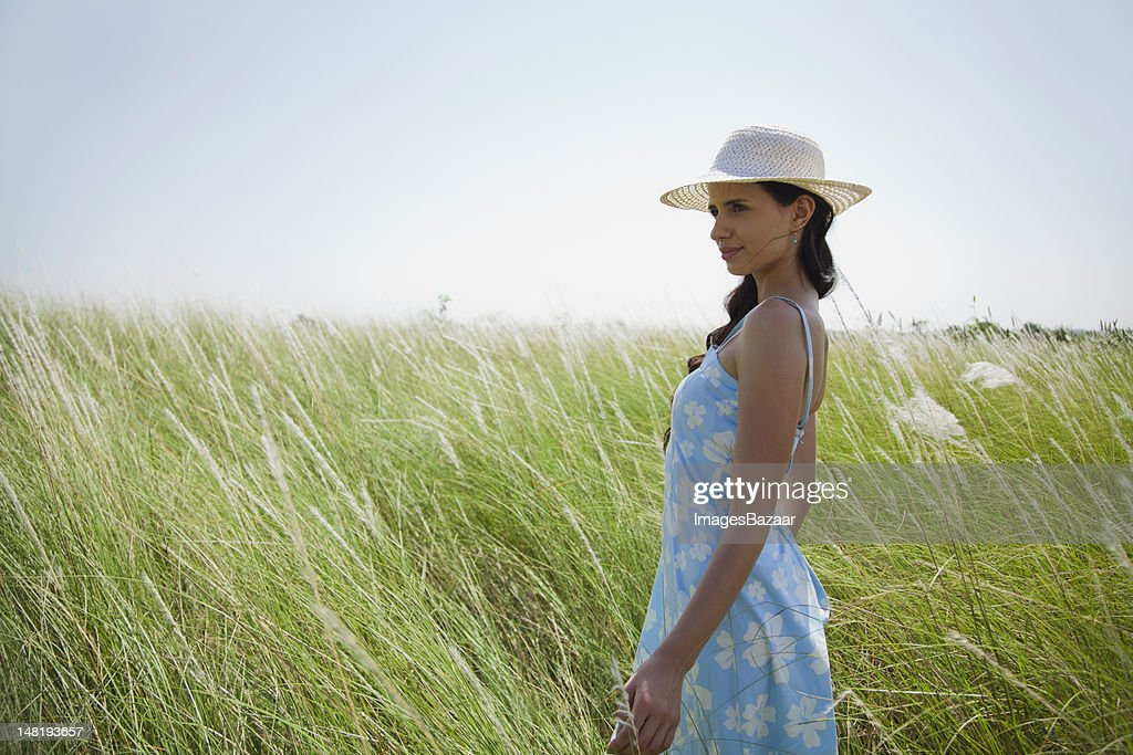 Portrait of young woman standing on meadow : Stock Photo