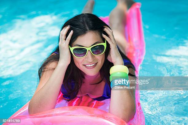 Portrait of young woman sunbathing on air bed in swimming pool