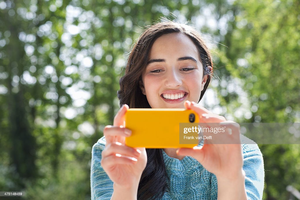 Portrait of young woman taking self portrait in garden : Stock Photo