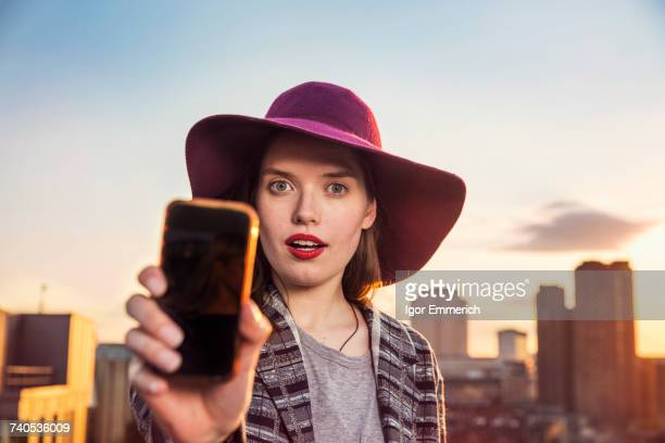 Portrait of young woman taking smartphone selfie at sunset roof party in London, UK