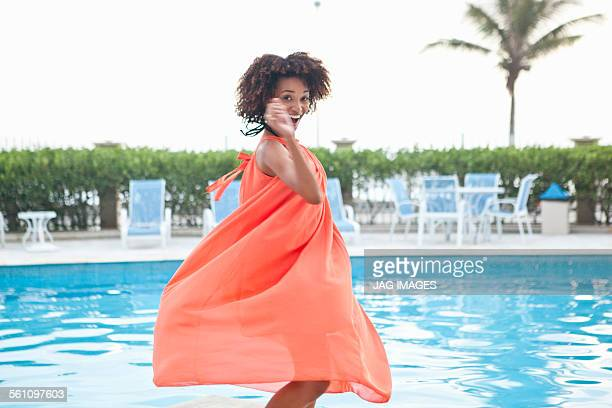 Portrait of young woman twirling in orange dress at hotel poolside, Rio De Janeiro, Brazil