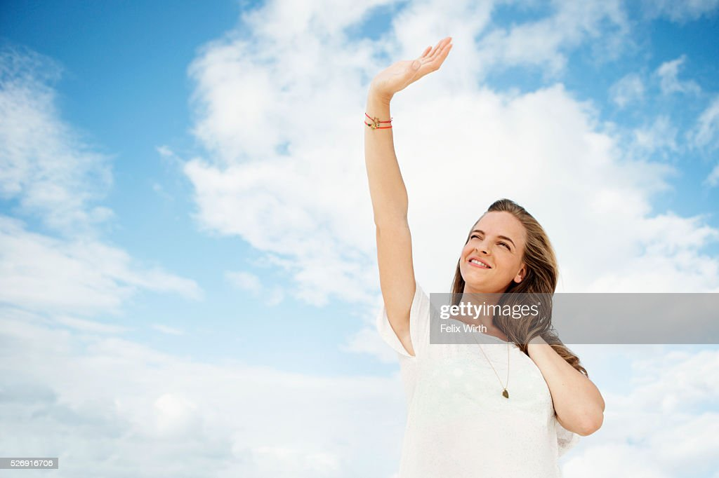 Portrait of young woman under blue sky with white clouds : Stock Photo