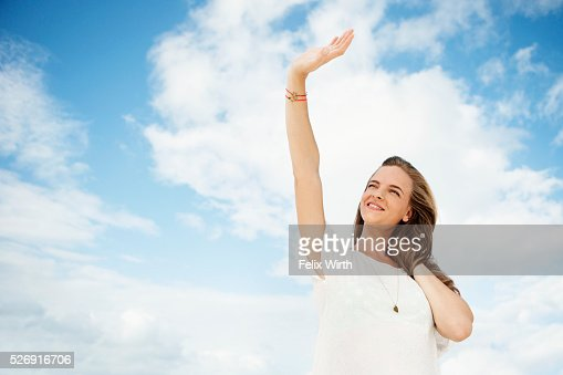 Portrait of young woman under blue sky with white clouds : Stockfoto