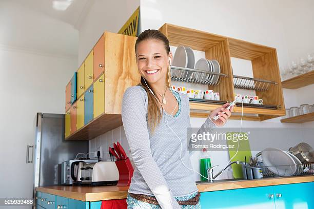 Portrait of young woman using mp3 player at home