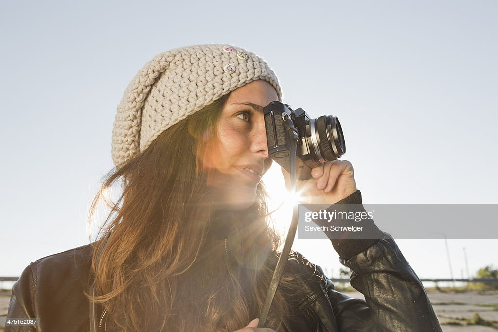 Portrait of young woman using slr camera : Stock Photo
