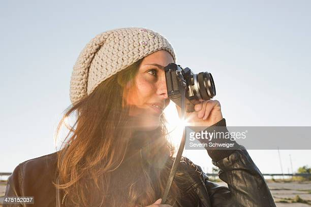 Portrait of young woman using slr camera