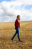 Portrait of young woman walking in harvested field