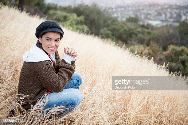 Portrait of young woman wearing a cap on grassy hill