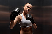 Portrait of young woman wearing boxing gloves