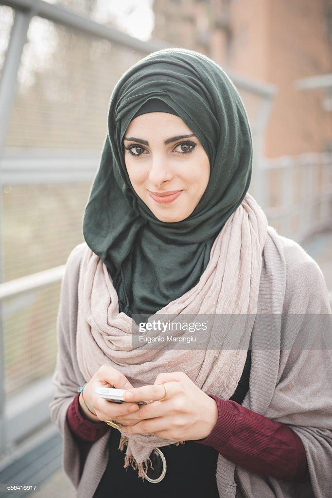 Portrait of young woman wearing hijab on footbridge