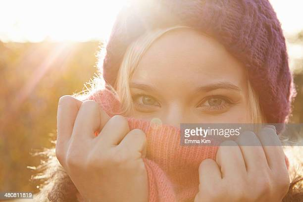 Portrait of young woman wearing knit hat, mouth covered