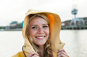 Portrait of young woman wearing rain coat at the waterside