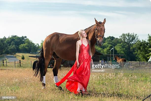 Portrait of young woman wearing red evening dress standing beside a horse on a meadow