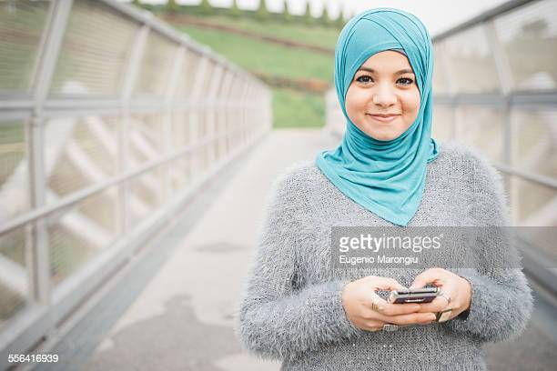 Portrait of young woman wearing turquoise hijab using smartphone on footbridge