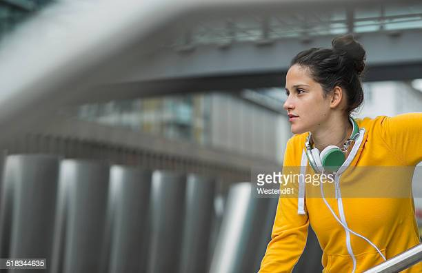 Portrait of young woman wearing yellow tracksuit top
